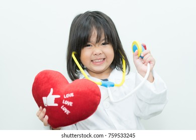 Little asian girl wear doctor uniform and smile with stethoscope holding big red heart on white background.check health and heart health concept.