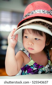little asian girl wear hat and she have boring face.