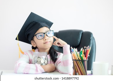 Little Asian girl wearing graduate hat hugging clear glass jar piggy bank and smile with happiness for money saving to wealthness succesful in the future of education concept select focus
