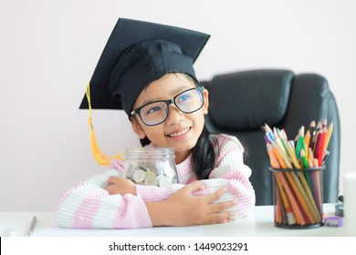 Little Asian girl wearing graduate hat hugging clear glass jar piggy bank and smile with happiness for money saving to wealthness succesful in the future of education concept shallow depth of field