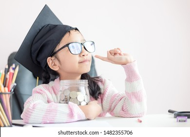 Little Asian girl wearing graduate hat hugging clear glass jar piggy bank and smile with happiness for money saving to wealthness succesful in the future of education concept