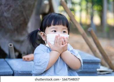 Little Asian girl wearing mask for protect air pollution and  virus when she stays outside. Baby shows hands gag coronavirus and epidemic virus symptoms. Covid-19 and Air pollution pm2.5 concept