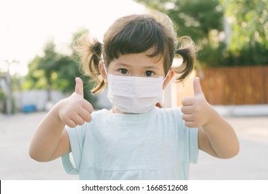 Little asian girl wearing mask for protect pm2.5 and show thumbs up gesture for good air outdoor.Air pollution pm2.5 and Coronavirus concept