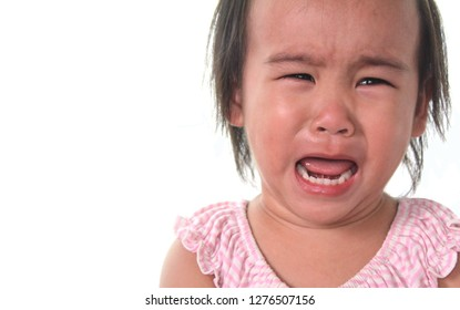 A little Asian girl wearing a pink shirt is crying to see the teeth and tongue. sad emotion on white background.