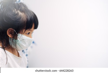 Little asian girl wearing a protective mask in school
