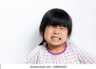 Little Asian girl wearing pyjamas doing silly face