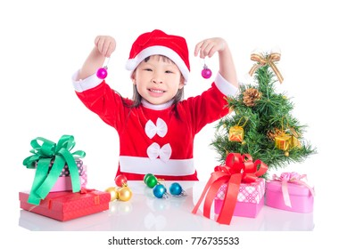 Little asian girl wearing santa claus dress decorating Christmas tree with balls over white background