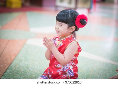 Little Asian girl wishing you a happy Chinese new year