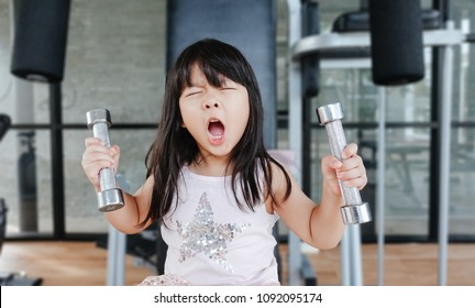 Little asian girl working out with dumbbells at gym and tired face.