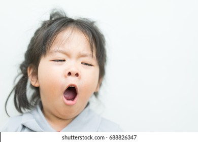 Little asian girl yawning on a white background.