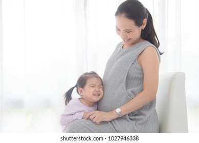 Little asian girlhugging her pregnant mother belly and smiles at home