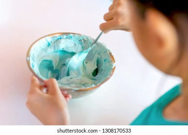 Little Asian girls beating a mixture of cream and blue food coloring in a mixing bowl at a kitchen table during cooking classes. Kid mixing whipped cream and food coloring during a baking workshop.