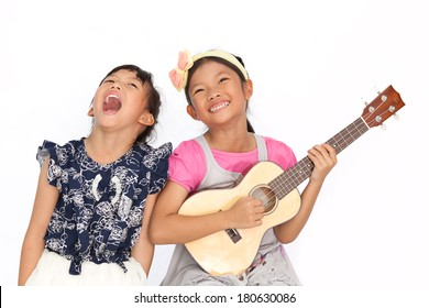 Little asian girls sing a song and playing ukulele isolate on white background