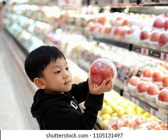 The little Asian kid choosing an apple in supermarket background with many fruit on shelf. Portrait handsome boy pickup big red apple in retail store. Concept of shopping, healthy food, sell and buy