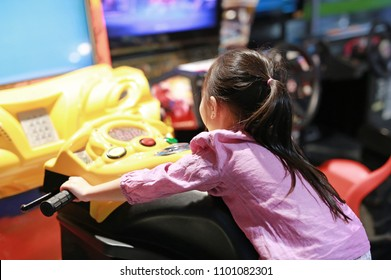 Little Asian kid girl playing arcade video game. Motorcycle Racing.