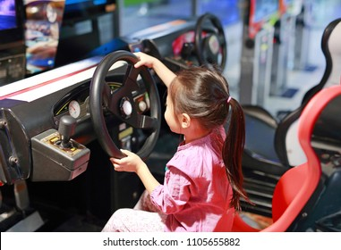 Little Asian kid girl playing arcade video game. Racing car.