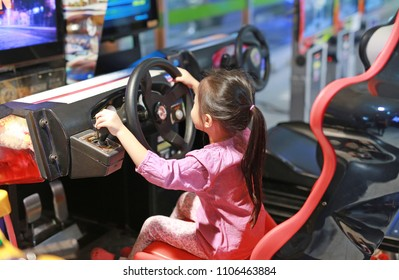 Little Asian kid girl playing game arcade Racing car.