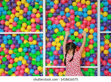 Little Asian kid girl playing climb on cage of playground colorful toy ball. Rear view.