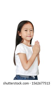 Little asian kid girl praying isolated on white background with copy space. Sawasdee is meaning hello.