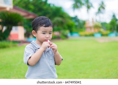Little Asian kid at the playground under the sunlight in summer, shallow DOF