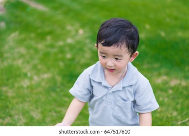 Little Asian kid at the playground under the sunlight in summer, shallow Focus