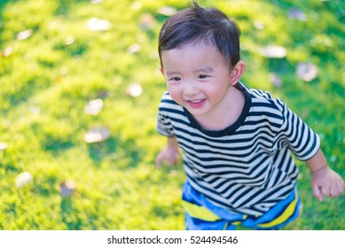 Little Asian kid playing and smiling at the playground under the sunlight in summer, Kids play on school yard. Happy kid in kindergarten or preschool. shallow DOF