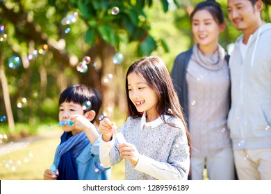 little asian kids boy and girl sister and brother blowing bubbles in a park with parents watching from behind.