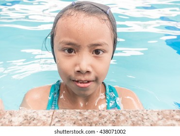Little asian kids girl in swimming pool. Summer outdoor.