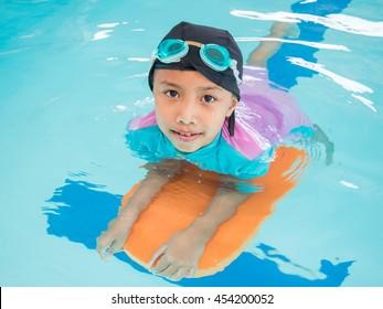 Little asian kids girl in swimming pool. Summer outdoor.