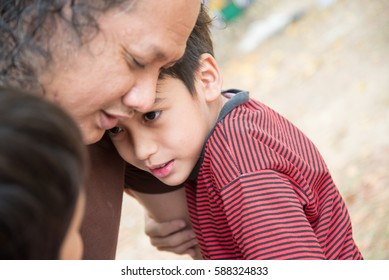 Little asian mix race boy with sad face , father hugging to support him