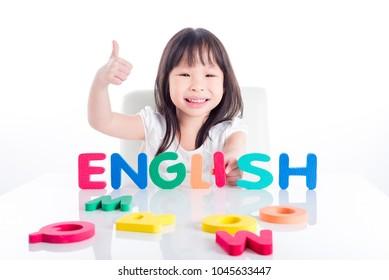 Little asian preschool girl making english word by her alphabet toy over white background