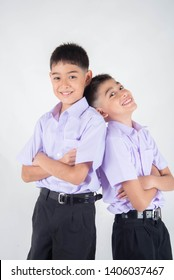 Little Asian sibling boys in student uniform pose together on white background