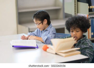 Little Asian spectacles Boy and his happy African boy. Happy Children Learning Class in Library. Development of Human Resources in Education Concept. Setup studio shooting.