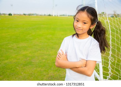 Little asian sport girl enjoy posing playing football on field