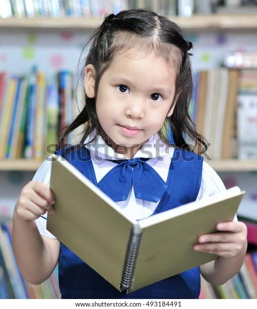 little asian student girl read a book background bookshelves