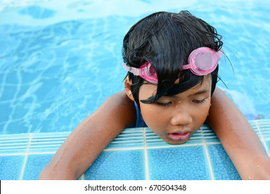 A little Asian swimmer girl  take a rest after swimming , So tired and sad beside swimming pool , has a swimming glass on her head.