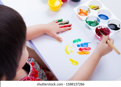 Little asian (thai) girl doing fingerprints using multicolored drawing tools (watercolor paints, paintbrush), learning, education of art and creativity concept, studio shot