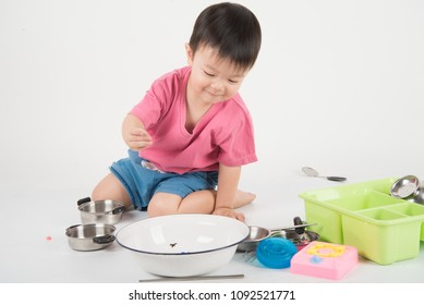 Little Asian toddler 2 years old playing kitchen toy