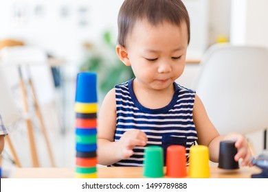 Little asian toddler boy playing stacking cups learning materials in a montessori methodology school being manipulated by children.Montessori classroom for the learning of children in mathematics.