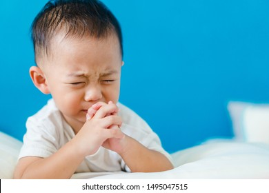 Little asian toddler boy praying and worship to GOD in bedroom in night time.Kid pray to GOD.Hand praying and palm up,Concept Praise and worship with faith, spirituality and Surrender.