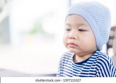 Little asian toddler boy wear hat and yawning in winter time.2 years old boy make sleepy face and tired face.