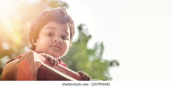 Little Asian/Indian kid playing slide at the playground under the sunlight in summer