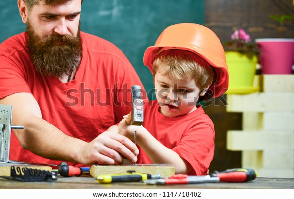 Little assistant concept. Father with beard teaching little son to use tools, hammering, chalkboard on background. Boy, child busy in protective helmet learning to use hammer with dad.