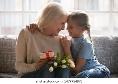 Little attentive granddaughter and elderly grandmother cuddling sitting on couch celebrating granny birthday anniversary with white spring flowers tulips and gift box, life events best wishes concept