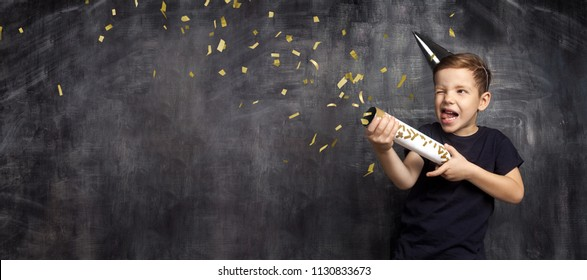 Little attractive boy with festive cap and flapper. Funny guy with slapstick in hands posing in front of blackboard. Concept of holiday and party.