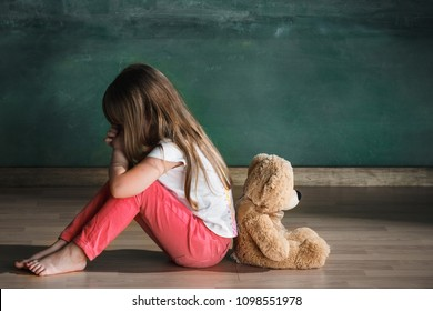 Little autistic girl with teddy bear sitting on floor at empty room. Autism concept. Conceptual image with little caucasian model at studio. Side view