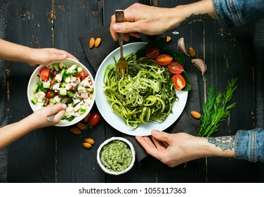 Little baby and adult young woman hands having a dinner or lunch with zucchini raw vegan pasta, avocado dip suace, vegetables fresh summer salad. Top view. Vegetarian healthy food. Organic product.