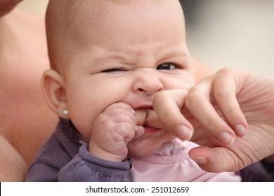 little baby biting her mother finger