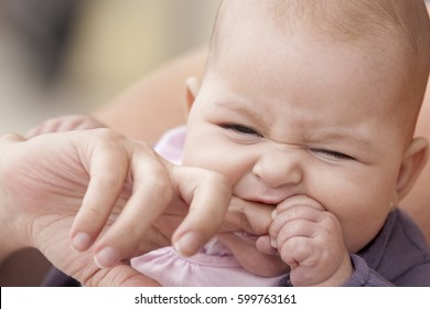 little baby biting her mother finger