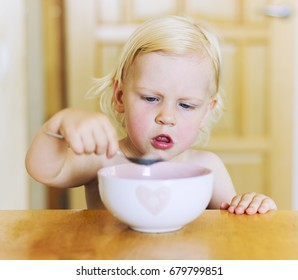 A little baby with blond hair eats healthy food from a white plate. Little cute girl eating porridge.